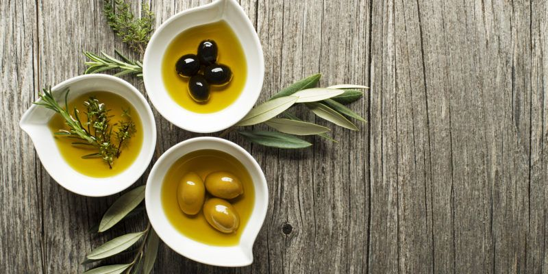 Olive oil with fresh herbs on wooden background